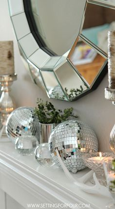 Disco balls, antlers and vintage crystal mixed with boxwood and lots of white! Mantel Decorating Ideas - sparkle and shine mixed with rustic simplicity. www.settingforfour.com
