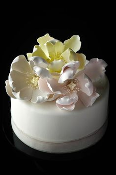 A satin ribbon and pastel sugar flowers give a polished finish to this simple white cake.