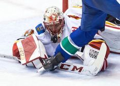 Calgary Flames goalie Mike Smith stops Vancouver Canucks' Sven Baertschi, of Switzerland, during the second period of an NHL hockey game in Vancouver, British Columbia, Saturday, Oct. 14, 2017. (Darryl Dyck/The Canadian Press via AP)