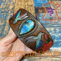 Welcome to see more pictures of this bright #handpainted #tooledleather #cuff #bracelet with #hummingbirds and #roses in my #Etsy shop #Gemsplusleather 😌 #Gemsforall #leathercraft #Leatherwork #artisan #artisanjewelry #leatherjewelry #instajewelry #jewelrygram #gemstonejewelry #jewelry #leatherjewelry #leatherart #labradorite #giftforher #lavkacraft #handmadejewelry #gemstonejewelry #instamood #instadailyphoto #instadaily #leather #hummingbird #rose #redrose Tooled Leather, Leather Cuffs, Leather Necklace, Leather Tooling, Leather Jewelry, Artisan Jewelry, Handmade Jewelry, Handmade Items, Leather Gifts For Her