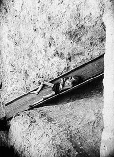 A corpse slides down a shoot into a mass grave in the Warsaw ghetto