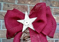 Burgundy burlap bow centered with a heavy, white iron star.