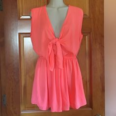 Beautiful Romper Beautiful Romper by San Joy. NWT- Never worn before! Size Medium. Color is Coral. The back has a silver accent piece and the front falls low with adjustable ties. Perfect for the beach with a nice tan! Dresses