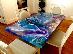 Contemporary artist Bich Nguyen mixes acrylic paint and resin to create mesmerizing swirls of color, which appear like brightly hued hot springs seen from above, or perhaps nebulae given the tie-dye treatment. Her most astounding recent work is a five-by-three-foot wooden panel that she's mounted on glass legs to create a table almost too dazzling to use. The tones in the piece—deep blues, purples, greens, and aquamarines mixed with soft streaks of white and splatters of gold—seem to twist…