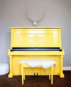 This look! Yellow statement piano, antlers above, and fur on bench!