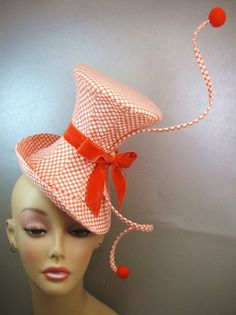 Sarah Padgham: My polka dot hat is made from orange polka dot microfiber cleaning cloth. I found it in my local grocery store and fell in love with the print. The top hat is constructed with 10 cut panels that form the shape of the hat. The hat is supported using buckram and sewable boning. The lining of the hat is black cotton twill. The trim is created also with sewable boning and millinery wire. I made the orange balls with wool felt. The hat is finished off with a velvet orange ribbon. E...