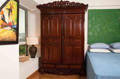 A splendid Dutch colonial cabinet in mahogany with details in ebony. The pediment is embellished with a cresting piece which is pierced and carved with floral motifs and centered with a peacock. The doors and sides constructed with fielded panels. The lower section of the cabinet has three drawers and an apron with beautifully carved foliage centered with a flower head. The legs are in a traditional Dutch style with a bulbous top, tapering, with a ring and ending in a peg foot.