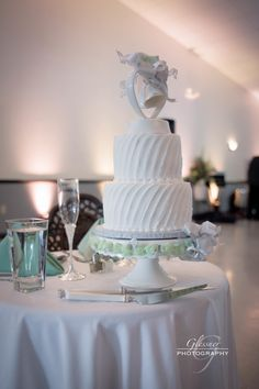 A white wedding cake with a sweet bell topper, was placed at the bride and groom's table at the Bakersville Banquet Hall in Pittsburgh. // johnparkerbands.com