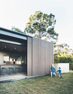 Sliding eucalyptus-wood screens wrap exterior of house on Australia's Sunshine Coast