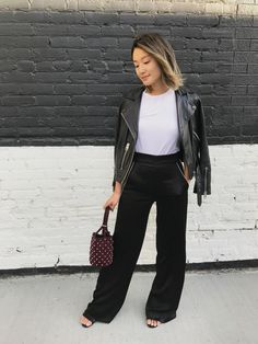 Friday - I want an edgier look as I'm meeting friends when the clock strikes six. I dress up the tee with satin wide-leg trousers that read more luxe than black jeans. A moto jacket is a must for nighttime and a studded bag complements the downtown vibe.