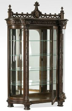 """19th century Gothic Revival carved oak demilune vitrine with an intricate pierce carved pediment featuring a carved monk's head at the center, surmounting a central glass door flanked by curved glass side panels, the interior with a mirrored back panel and four glass shelves, 71""""h x 51""""w x 16""""d."""