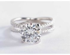 This platinum engagement ring features two French pavé-set bands that form a reverse split shank.