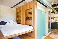 "Silo House puts on a clinic in how to decorate round rooms, and gives another answer for the perennial question ""Where should I put the bed?"" With a few turns of a hand crank, this platform bed disappears into the ceiling. The bathroom is in the hallway between the bedroom and kitchen, whose center island contains a sink, stove, convection oven, refrigerator, and dishwasher—and can be converted into a large dining table."