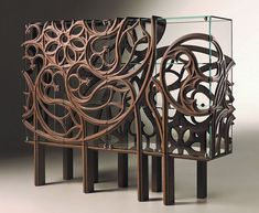 Designed by Ferruccio Laviani and manufactured by Italian company Fratelli Boffi, Gothik-A Cabinet envelops glass case with decorative wooden design.