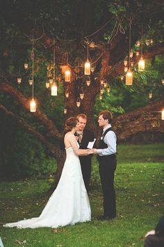 Frascos de cristal colgando con velas para decorar la boda