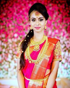 South Indian bride. Gold Indian bridal jewelry.Temple jewelry. Jhumkis.Red pink silk kanchipuram sari.Side braid with fresh jasmine flowers. Tamil bride. Telugu bride. Kannada bride. Hindu bride. Malayalee bride.Kerala bride.South Indian wedding.