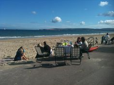Typical summer Sunday afternoon on Poole beach, Dorset hanging outside the beach hut.