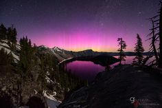 A pink aurora shines over Crater Lake, an ancient volcanic caldera in Oregon.