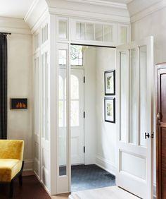 aménagement entrée avec porte vitrée, moulures blanches et déco sobre