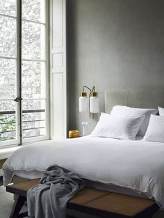 Architect Joseph Dirand's bedroom boasts sandy gray walls and upholstered headboard. The white bed linens help reflect daylight into the space and the Azucena sconces offer task illumination.  Courtesy of Ryland Peters & Small.