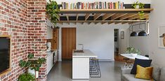 Exposed brick, white kitchen, timber mezzanin with book shelf, concrete floor, touches of black. Kitchen Store, Showcase Design, Exposed Brick, Concrete Floors, Discount Furniture, Eames, Cool Kitchens, Bookshelves, Furniture Design
