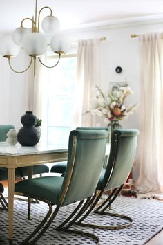 Reupholstered dining chairs in green and brass cantilever chairs by Pierre Cardin in eclectic modern dining room. Modern chandelier and 1950s French marble pastry table used as dining table. Mixing vintage with new.