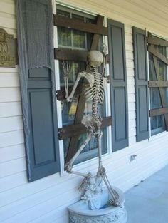 Cardboard affixed to window to make it look boarded up and skeleton proped to look like it's trying to get in!
