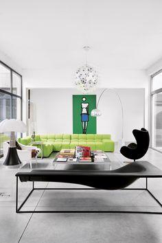 涅槃的艺术#你我家生活#亮绿色的沙发(Patricia Urquiola 设计,B&B Italia 出品)和黑色躺椅(Cappellini 出品)仿佛在对话,Taraxacum 经典吊灯、Castiglioni 的落地灯和Gae Aulenti设计的Bat台灯(Martinelli Luce 出品)似乎也加入了讨论。这些家具与雪白的墙面相得益彰,也与微微泛光的混凝土地面配合得天衣无缝。远处的墙上挂着的是著名英国视觉艺术家Julian Opie的作品。