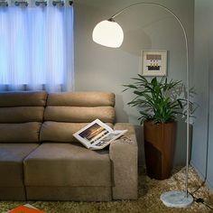 Sala com paredes cinza, sofa bege e luminaria redonda arco.