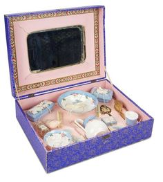 """13"""" (33 cm.) x 10"""" box. The wooden box with lithographed paper cover has colorful engraving on the lid, and hinges open to reveal a well-fitted interior with rose paper lining and mirrored back. Inside is a porcelain toilette service with blue edging on white ground, painted pink roses, and gilt edging, comprising wash bowl and pitcher, three covered boxes and jars, bowl, and a variety of accessories including cologne bottle, powder puff, paper-wrapped soap and more. Excellent condition…"""