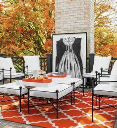 tapis d'extérieur -orange-motif-blanc-salon-jardin-metal-noir-coussins-galettes-blanc-cheminee