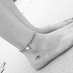 Tatuaje de ola minimalista en el pie