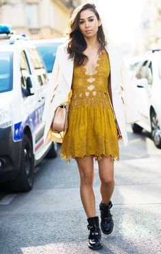 Rumi Neely in a mustard eyelet dress, whte blazer, and black boots
