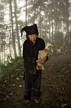 Woman carrying her duck, China