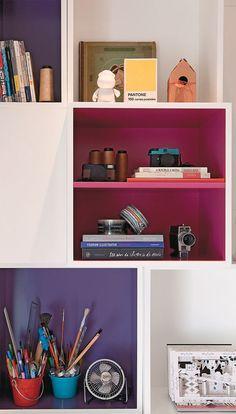 Os módulos da estante, executada pela Marcenaria Cardoso de Andrade, reproduzem algumas cores. Por trás da estante a porta do banheiro.