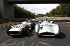 Formula One drivers Nico Rosberg and Michael Schumacher drive classic Silver Arrows.  Schumacher driving the W196 Streamliner and Rosberg driving the W196.