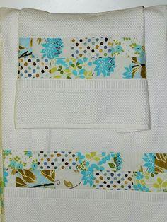 Juego de toallas blancas, ducha y lavabo. Decoradas con telas en tonos azul y verde oliva.  Precio: 40 €