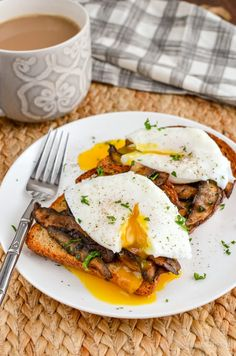 poached eggs over garlic mushrooms on toast with parsley and a mug of coffee