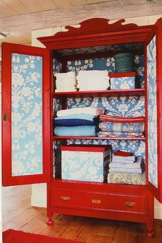 Red painted wardrobe, with blue wall paper.