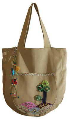 Bolsa em lona 100% algodão. Forro 100% algodão e bolso interno. Detalhe de bolsão externo bordado e penduricalho decorativo. Tamanho aproximado: altura 39cm, largura 32cm, profundidade 7,5cm e alça 52cm. R$ 45,00