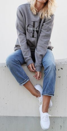 Mija is wearing a grey logo sweater from Calvin Klein, vintage jeans from Acne Studios and white vans