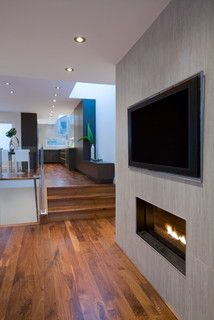 fireplace wall with tv above.  wall is built out so that tv is flush.