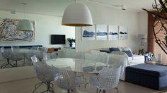 Sala de jantar integrada com mesa oval branca Saarinen + cadeiras de acrílico Meridiana + pendente Bertolucci (adoro esta luminária!). Projeto Diego Revollo, via Uol Casa.