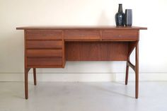 Teak Danish writing desk featuring six drawers and moulded applied legs