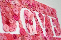 Button Art – Pink Ribbon Love Plaque. I've never seen one that uses the negative space like this. Love it! Maybe I could do one with our last name. #buttons #pinitparty
