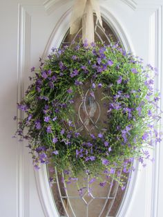Beautiful artificial small purple flower door wreath with a burlap ribbon on a grapevine wreath