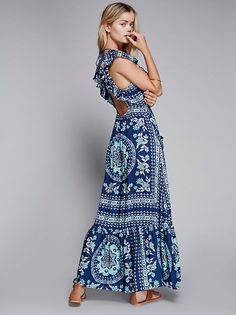 Frill Printed Maxi Dress | Boho femme printed maxi dress in a flowy silhouette featuring ruffle detailing on the sleeves and hem. Open back with adjustable tie and tassel ends. Elastic band in back for an easy fit and front slip pockets.