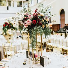 Wedding reception styling with gold stands, draping red and blush pink florals among luscious greenery, and mixed in with white and gold accents, in The Refectory
