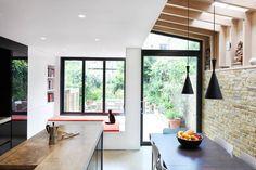 Duże okna i wyjście na taras sprawiają, że w tej kuchni zaciera się granica między wnętrzem, a ogrodem. Aby w pełni docenić walory pięknego widoku zbudowano wygodne siedzisko w kształcie litery L. Układ kuchni z wyspą sprawia, że nawet gotując można obserwować co dzieje się na terasie.
