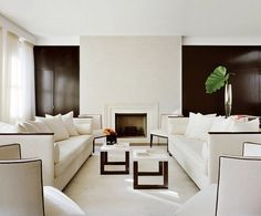 The contrast of the recessed black shiny wall against the white fireplace makes the living room feel like the wall continues to stretch off in the distance.